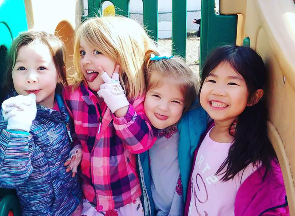 girls smiling in playground at a Preschool & Daycare Serving Carmel, Indiana