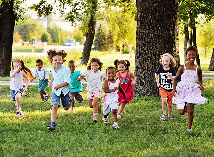 A group of happy children run in the Park at a Preschool & Daycare Serving Carmel, Indiana