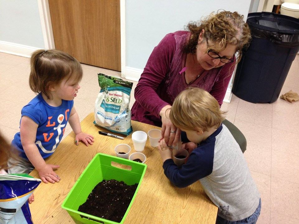 children and teacher planting seeds at a Preschool & Daycare Serving Carmel, Indiana