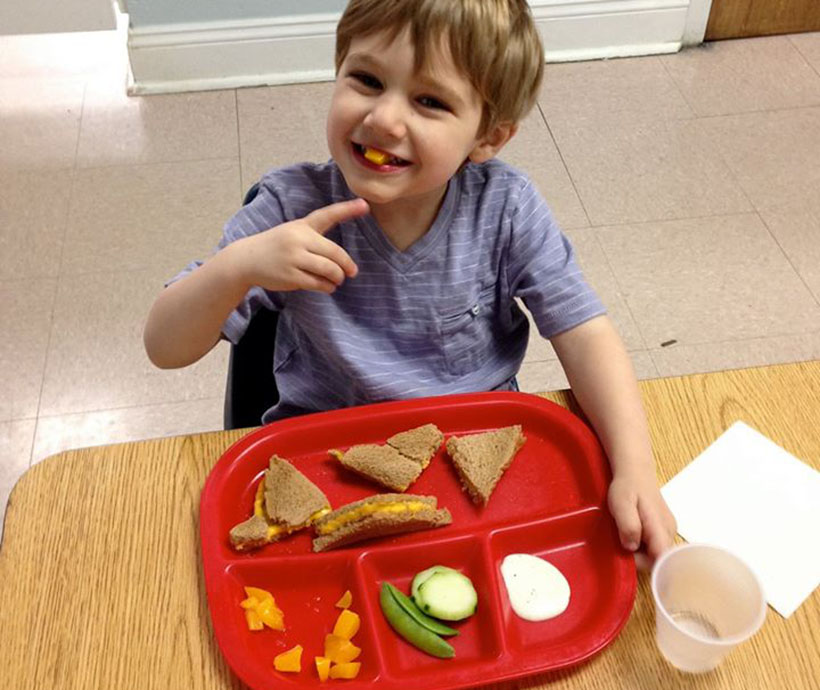 happy boy eating at a Preschool & Daycare Serving Carmel, Indiana
