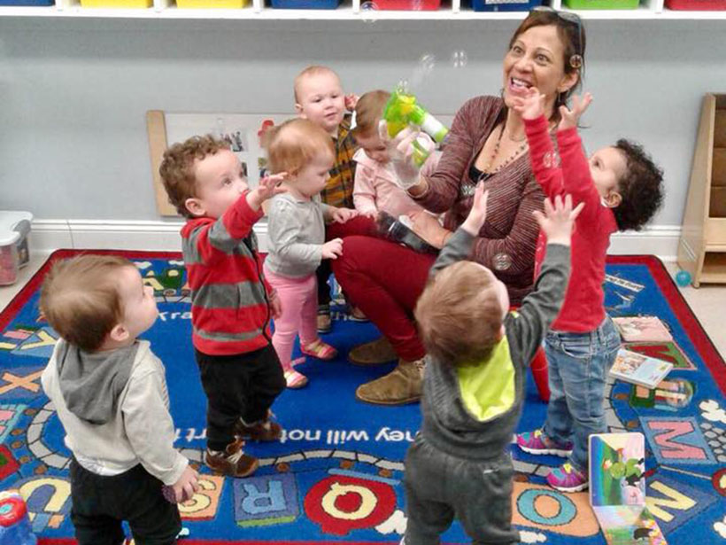 happy teacher and kids playing with bubbles at a Preschool & Daycare Serving Carmel, Indiana
