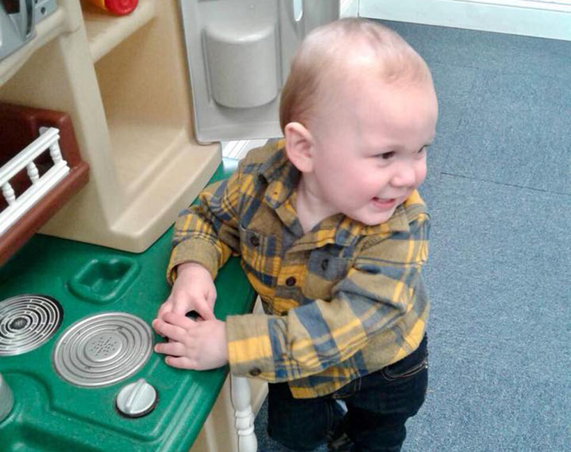 happy toddler in toy kitchen at a Preschool & Daycare Serving Carmel, Indiana
