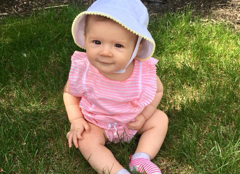 smiling baby sitting on grass outdoors at a Preschool & Daycare Serving Carmel, Indiana