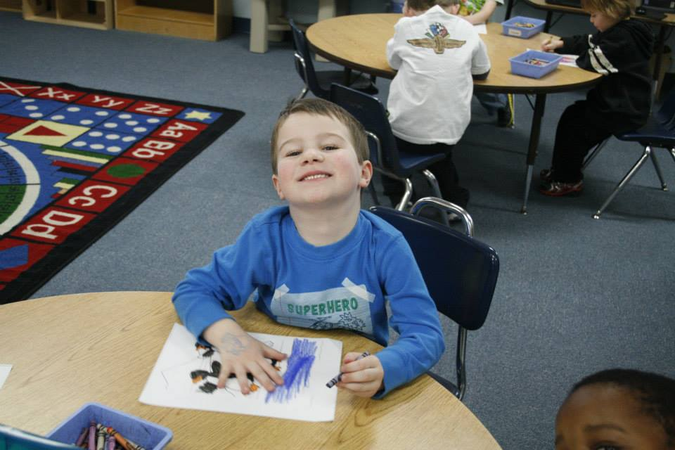 smiling boy coloring at a Preschool & Daycare Serving Carmel, Indiana