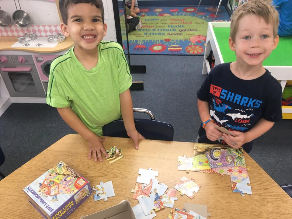 smiling kindergarten boys playing with a puzzle at a Preschool & Daycare Serving Carmel, Indiana