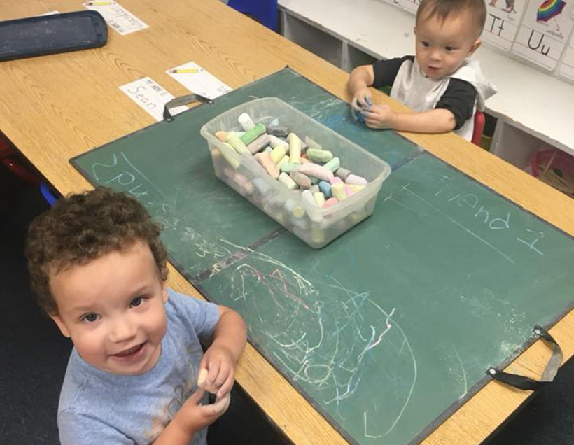 toddlers playing with chalk at a Preschool & Daycare Serving Carmel, Indiana