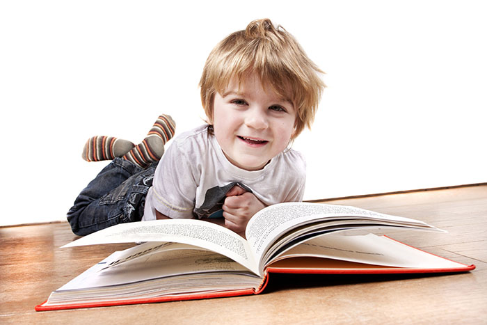 4 year old boy reading a book at a Preschool & Daycare Serving Carmel, Indiana