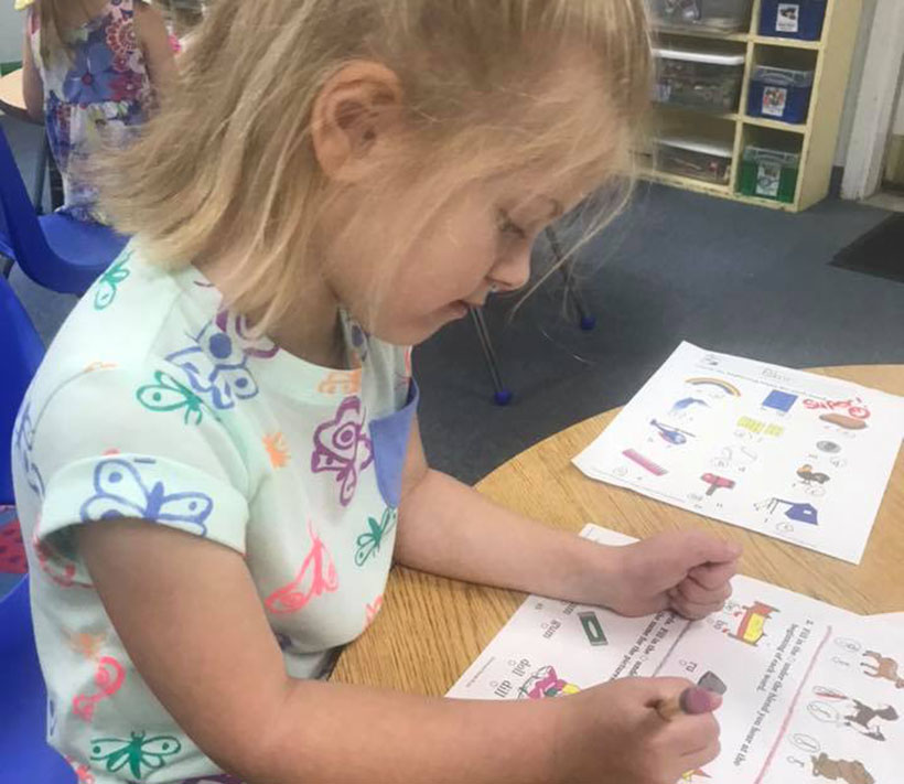 young girl doing homework at a Preschool & Daycare Serving Carmel, Indiana